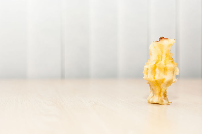 Apple eaten to the core upright on bright white background with low angle perspective. Apple Apple Core Bright Brown Core Decay Diet Eat Eaten Food Fruit Healthy Healthy Eating Light Low Angle View Natural Perspective Produce Rot Standing Table Top Upright Vertical White