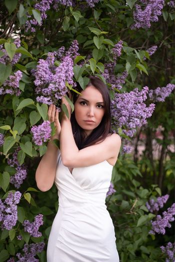 Portrait of beautiful woman standing against purple flowering plants