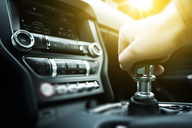 Close-up of man hand on gearshift in car