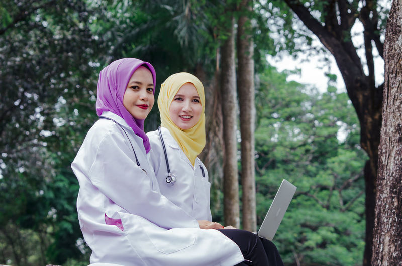 Portrait Of Female Doctors Using Laptop Against Trees