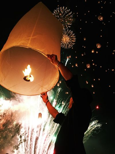 Low angle view of man releasing lantern in the dark