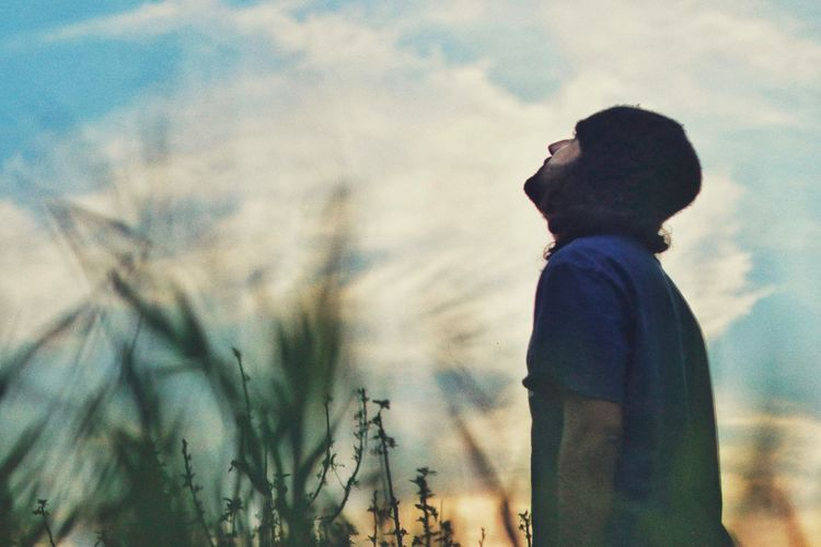 Side view of man looking at camera against sky