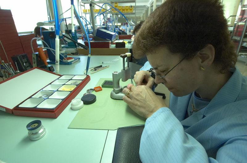Female watch maker working in industry