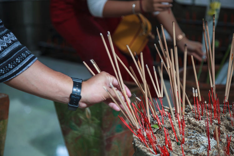 Cropped hand holding incense in temple