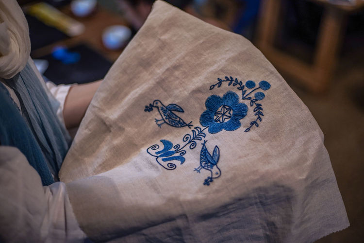 Midsection of person holding embroidered textile