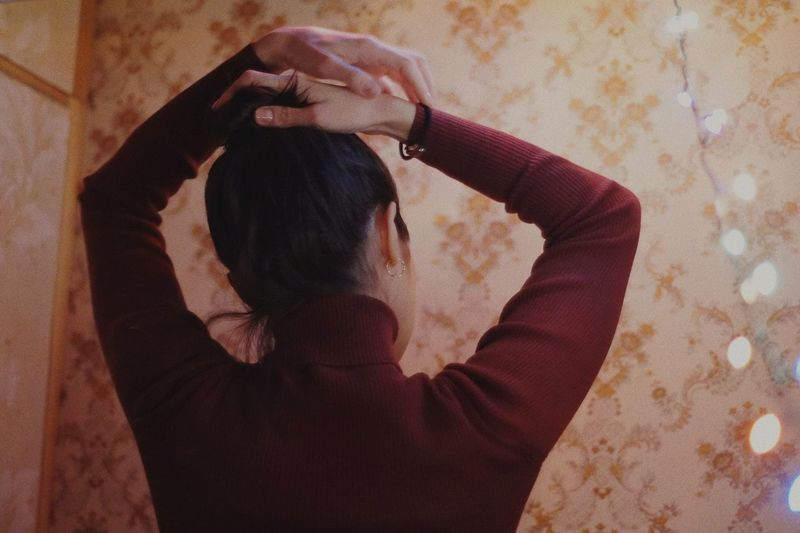 Rear view of woman with arms raised standing against wall at home