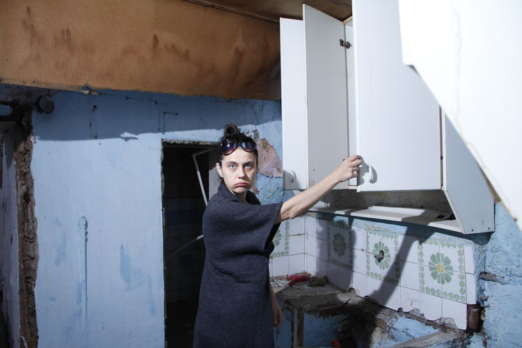 Portrait of woman making a face while standing against wall
