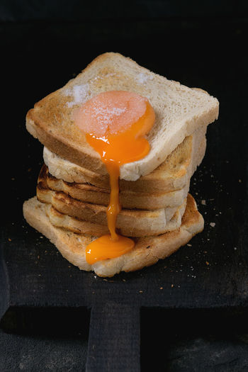 Stack of toasts bread with flowing sugared yolk on black wooden cutting board over black textured background. Breakfast Dessert Egg Yolk Sugar Toast Black Background Bread Breakfast Close-up Cutting Board Egg Food Food And Drink Fried Indulgence Ready-to-eat Sandwich Sugared Yolk Sweet Food Table Toasted Bread Unhealthy Eating White Bread Yolk