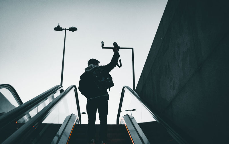 Low angle view of silhouette man standing by railing against sky