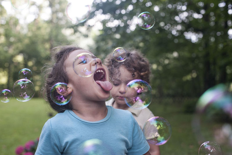 Boy playing with bubbles at park