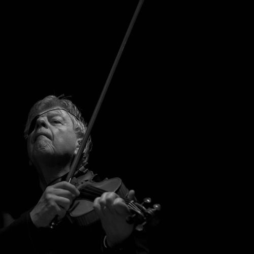 Senior man playing violin against black background