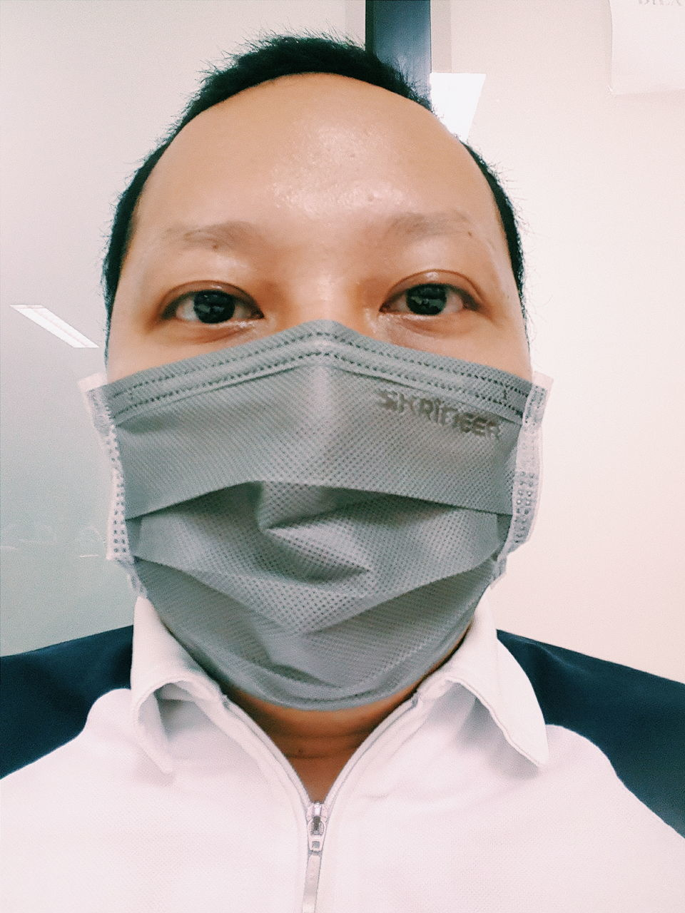 front view, looking at camera, head and shoulders, real people, portrait, surgical mask, one person, young adult, close-up, studio shot, headshot, young women, indoors, white background, needle, day