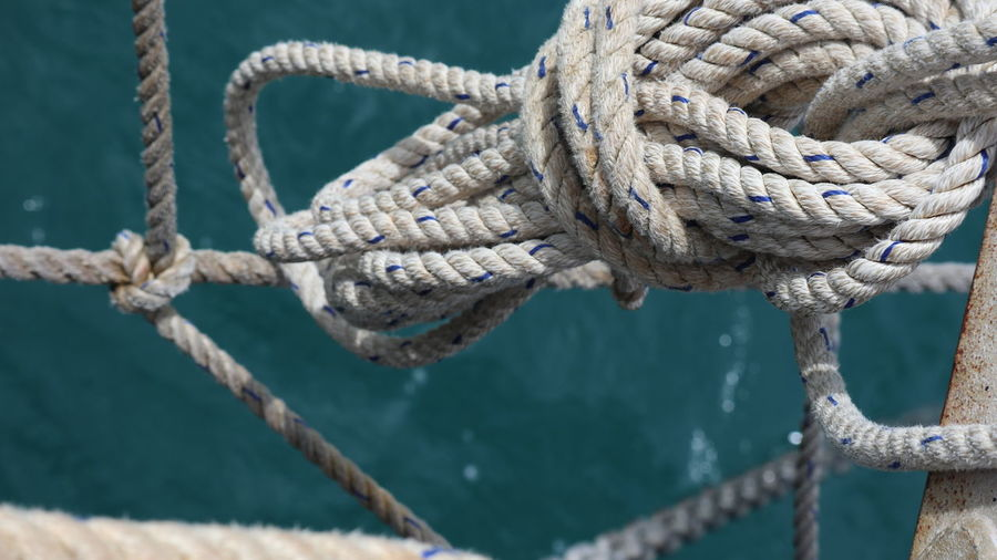 Close-up of rope tied to boat moored on sea