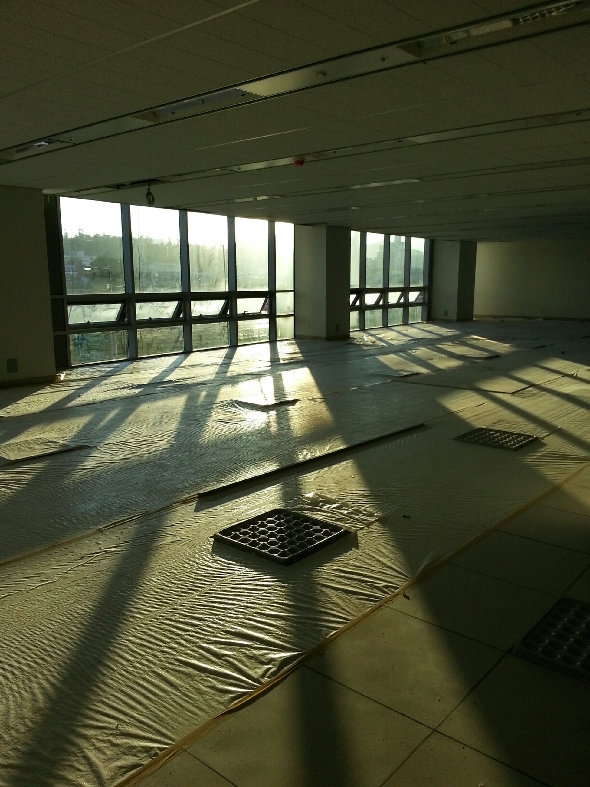 architecture, built structure, indoors, sunlight, shadow, ceiling, window, glass - material, architectural column, sun, flooring, no people, sunset, sunbeam, building exterior, sky, modern, day, reflection, empty