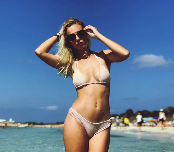 Portrait of young woman wearing bikini and sunglasses standing at beach during summer