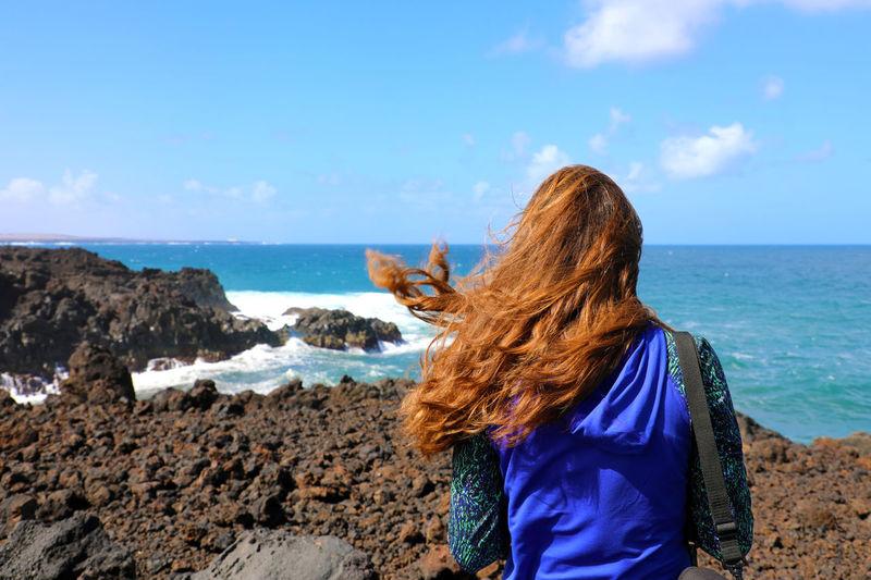 Woman in windy Los Hervideros, Lanzarote Wind Power Beach Beauty In Nature Hair Hairstyle Lifestyles Long Hair Los Hervideros Nature One Person Rear View Sea Sky Water Windy Yaiza