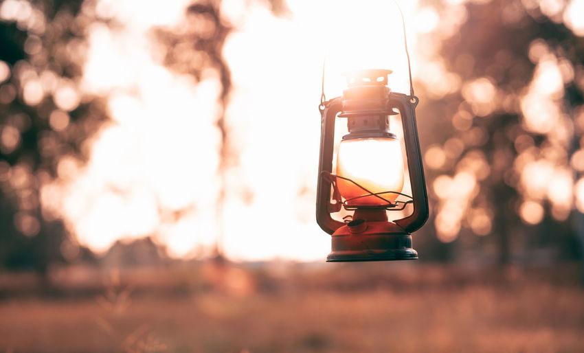 Close-up of illuminated lantern hanging against orange sky