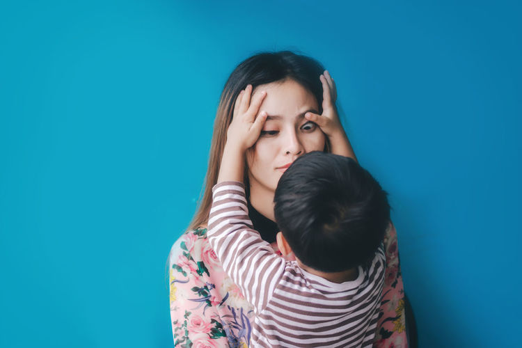 Adult Black Hair Blue Blue Background Bonding Casual Clothing Child Childhood Daughter Emotion Family Family With One Child Females Girls Indoors  Innocence Love Parent Positive Emotion Real People Sister Son Striped Togetherness Women