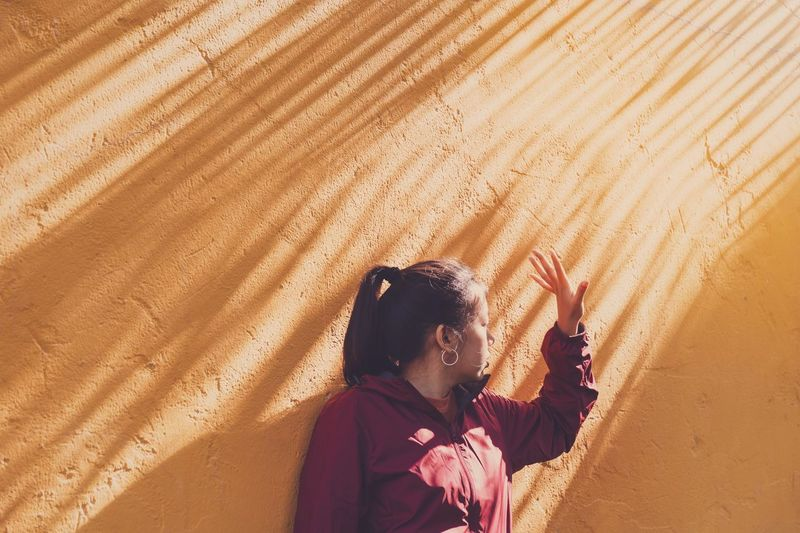 Woman Gesturing Standing Against Orange Wall