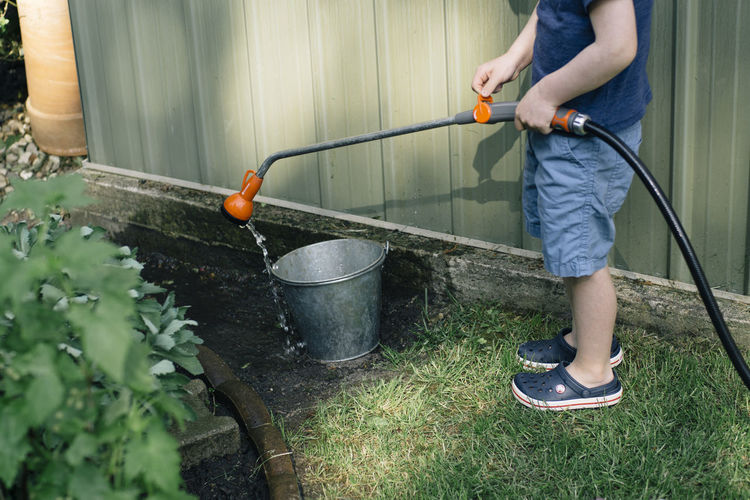 Low section of boy pouring water with garden hose in bucket at yard