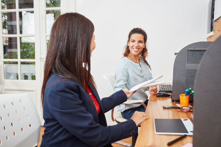 Businesswoman giving documents to female coworker at desk