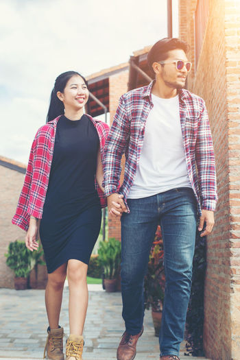 Architecture Casual Clothing Couple - Relationship Day Emotion Focus On Foreground Front View Full Length Fully Unbuttoned Happiness Leisure Activity Lifestyles Looking Away Outdoors People Positive Emotion Real People Standing Togetherness Two People Young Adult Young Men Young Women