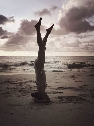 Side View Of Woman Performing Headstand On Beach Against Cloudy Sky