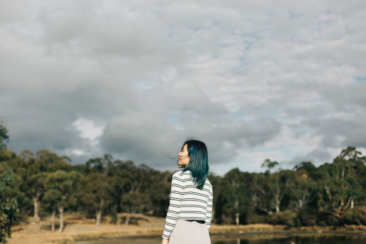 Cloud - Sky One Person Real People Sky Standing Lifestyles Leisure Activity Nature Young Adult Casual Clothing Striped Plant Young Women Day Beauty In Nature Tree Waist Up Adult Land Outdoors Hairstyle People Portrait Travel The Traveler - 2019 EyeEm Awards