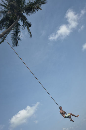 Low angle view of man swinging against sky