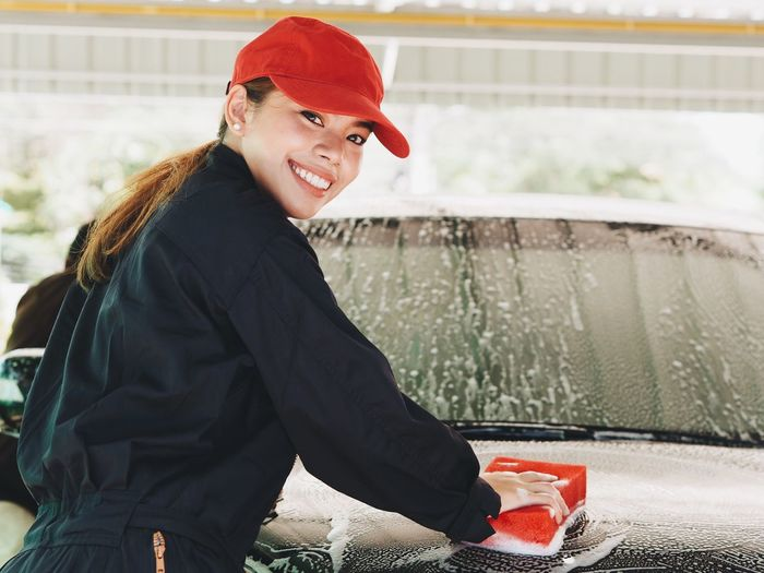 Portrait Of Smiling Young Woman Cleaning Car In Workshop