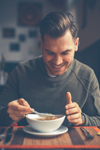 Smiling man having food at table in restaurant