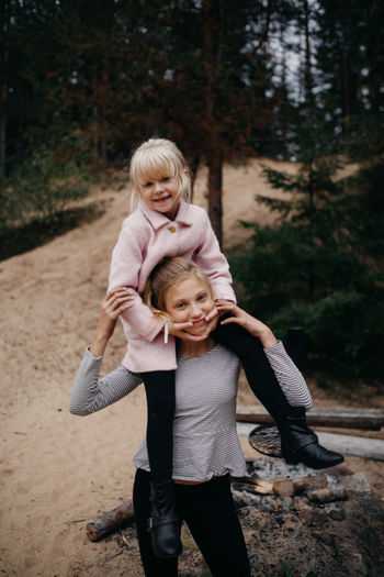Portrait Of Girl Carrying Sister On Shoulder