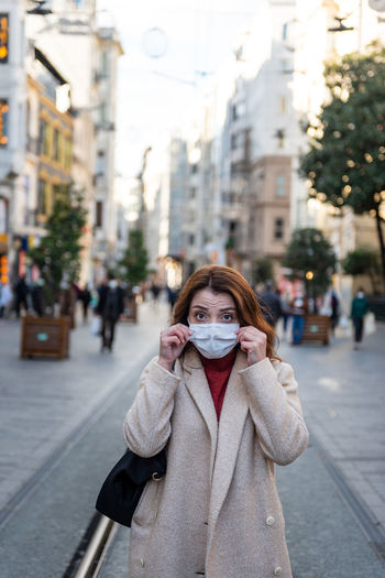 Portrait of woman wearing mask standing on city street