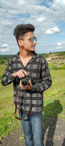 Young man photographing while standing on field