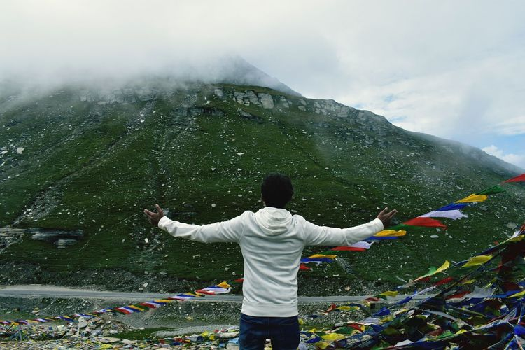 Rear view of man standing by prayer flags and mountain against sky