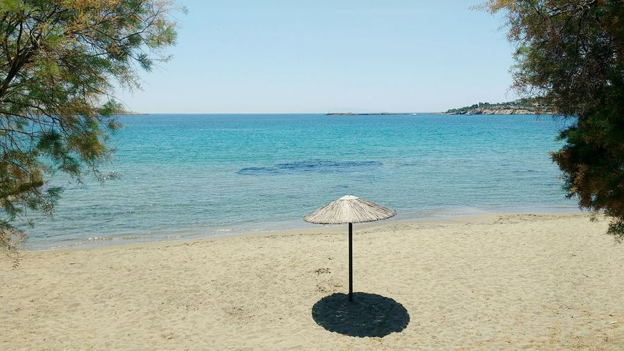 One lonely palapa on a beach waiting for tourists Beach Sand Water Sea Tranquility Nature No People Outdoors Clear Sky Scenics Blue Horizon Over Water Palapa Straw Umbrella Relax Lonely Beach Finikas Syros Greece Off Season Shade Round Shade Parasol Umbrella Quiet An Eye For Travel