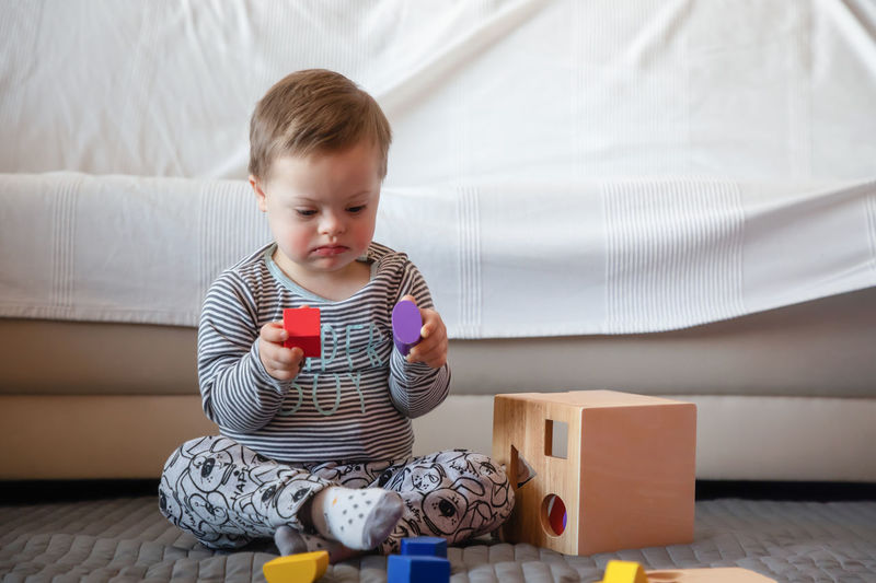 Babyboy Boys Child Childhood Cute Down Syndrome Front View Furniture Holding Home Interior Indoors  Innocence Leisure Activity Lifestyles Males  Men Mental Health  One Person Playing Real People Sitting Toy
