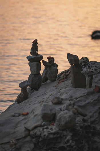 Stack of stones on shore during sunset