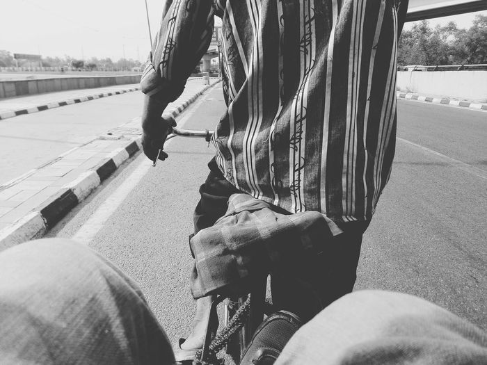 Low section of passenger and man on pedicab at road