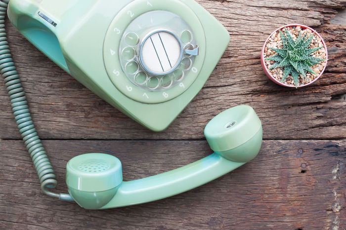 Retro background with rotary telephone on wood table. Phone Telephone Vintage Old Classic Retro Table Hotline Background Communication Contact Past Conversation Call Rotary Office Wood Cable Object Handset Texture Connect Communicate Talk Number Single Equipment Dirty Electronics  Cactus