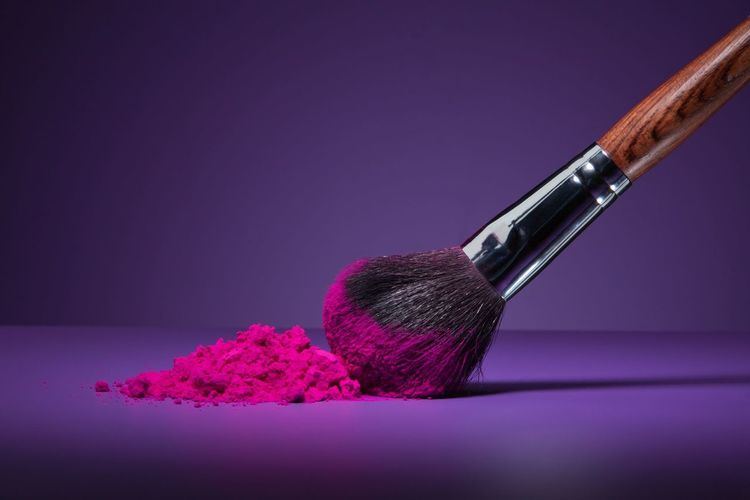Close-up of make-up brush and pink face powder on purple table