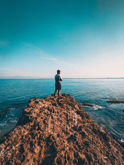 Man standing on rock by sea against blue sky