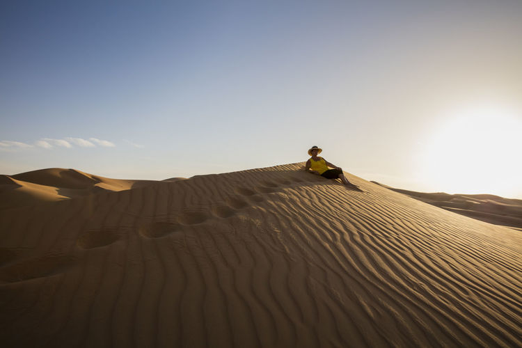 Senior woman relaxing at desert against clear sky during sunny day