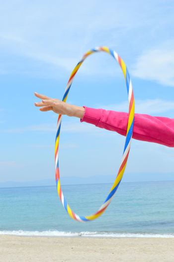 Female hand playing with hula hoop on the beach