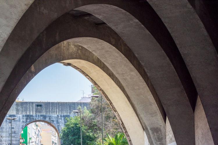 Arch bridge amidst buildings against sky