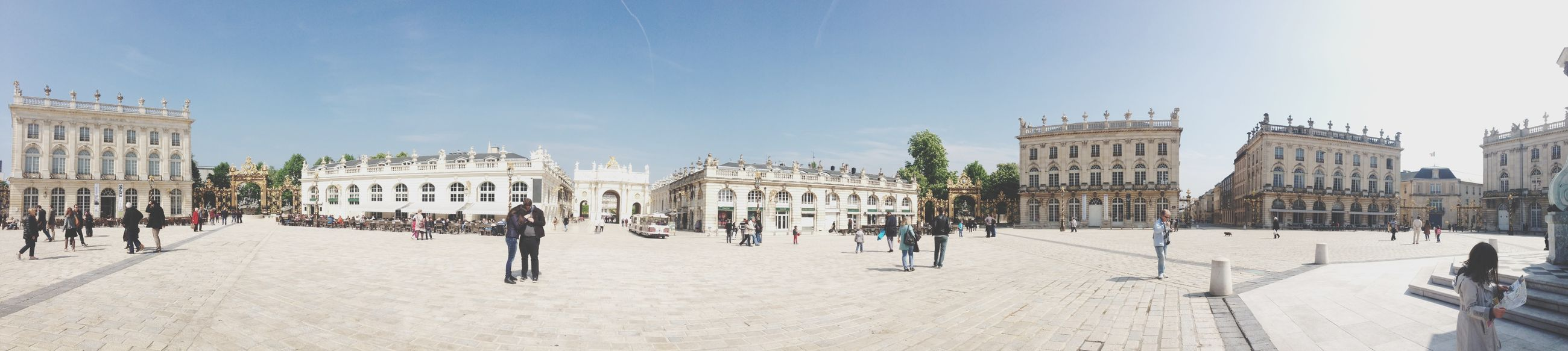 architecture, building exterior, built structure, sky, walking, men, sunlight, person, incidental people, clear sky, large group of people, lifestyles, tourist, day, town square, shadow, blue, city, leisure activity