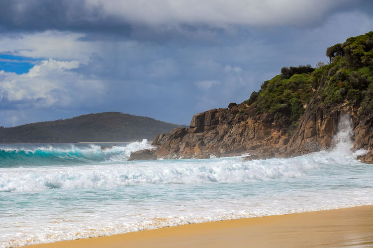 Waves crashing over rocky coastline against beach and stormy sky Australia Coastline Coastline Landscape Port Stephens Sky And Clouds Beach Beach Beauty In Nature Crashing Day Landscape Mountain Nature No People Ocean Outdoors Power In Nature Rocks Scenics Sea Seascape Sky Water Water Wave