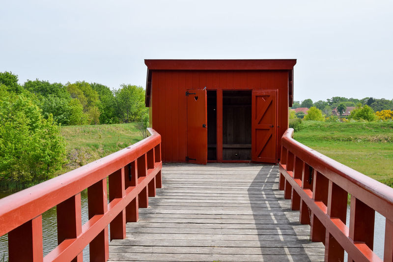 Empty wooden footbridge leading to built structure against sky