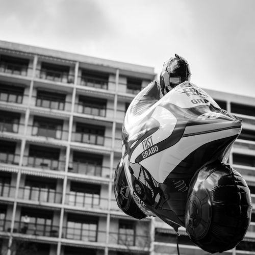 Fun Funny Surrealism Riding Speed Balloon Toy Motorcycle Motorbike Speed Helium Balloon Politics And Government Military City Sky Close-up Building Built Structure Residential Structure Motorcycle Racing Biker Exterior Office Building Building Exterior Racing Bicycle