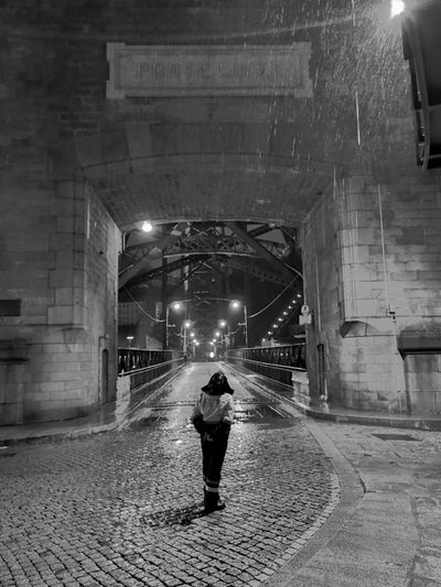 Rear view of woman walking on street at night